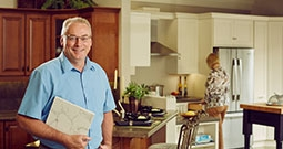 salesman stands with papers in showroom kitchen