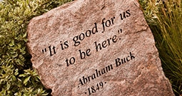 stone engraved with 'it is good for us to be here. Abraham Buck 1849'